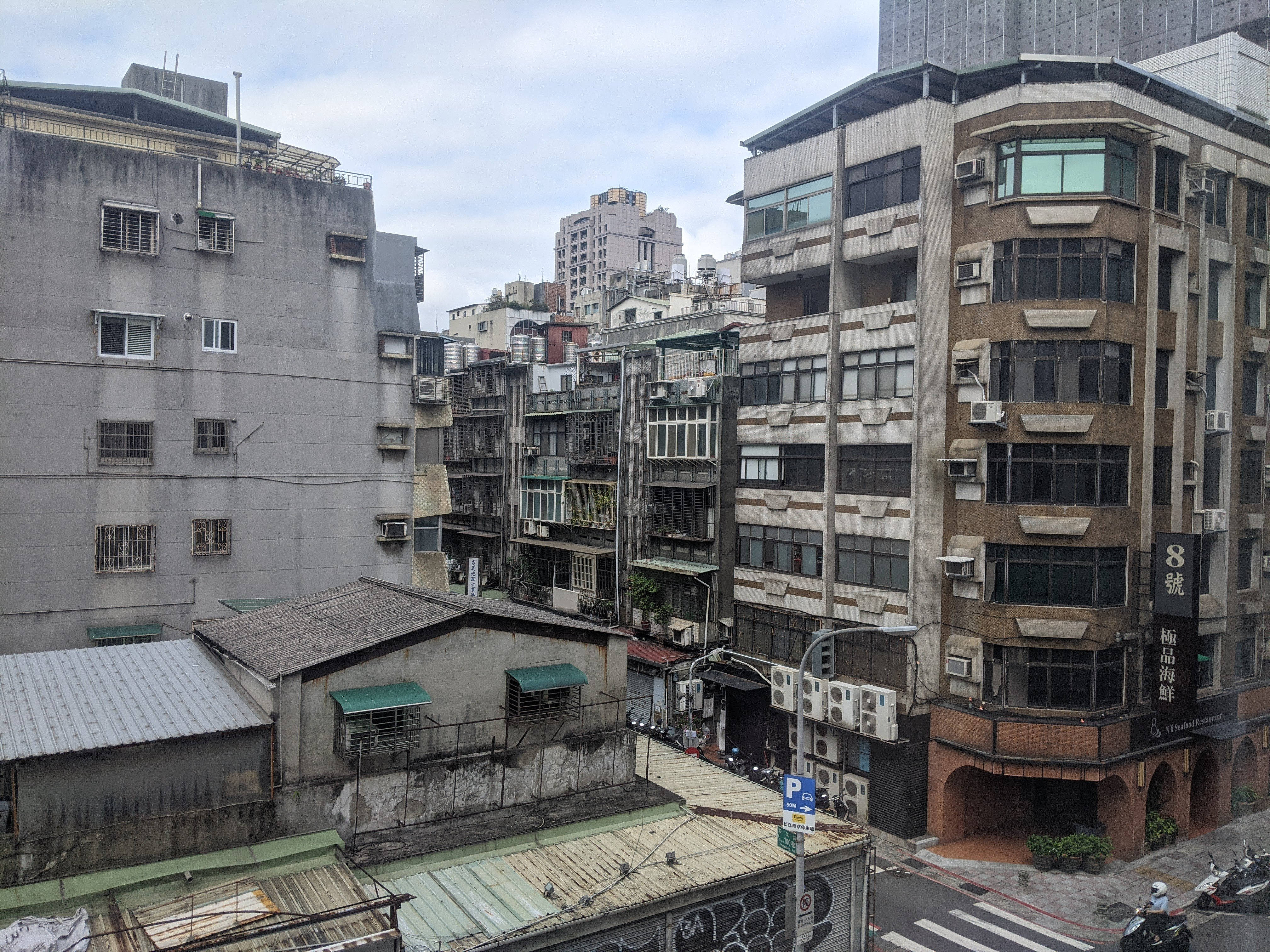 a view of several buildings in taipei, showing some balconies with plants on them
